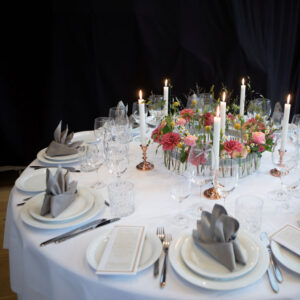 smukt dækket bord med blomster dekoration og lejede stole og borde